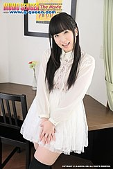 Leaning On Desk Long Hair Over Her White Dress Hands Clasped At Her Thigh