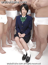 Student seated before semi naked men wearing uniform hands clasped on her lap short hair