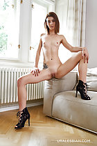 Tera sitting on sofa arm naked small breasts legs spread showing her shaved pussy in high heels